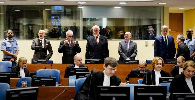 Slobodan Praljak (vierde van links) met aan de uiterste zijden twee bewakers die de verdachten continu in de gaten moeten houden.   Beeld EPA