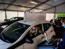'Stoeien' met het stembiljet in de auto in het drive-in stembureau