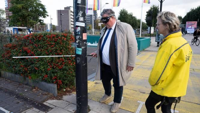 Op de Internationale Dag van de Witte Stok steekt burgemeester Bruls blind het stationsplein over