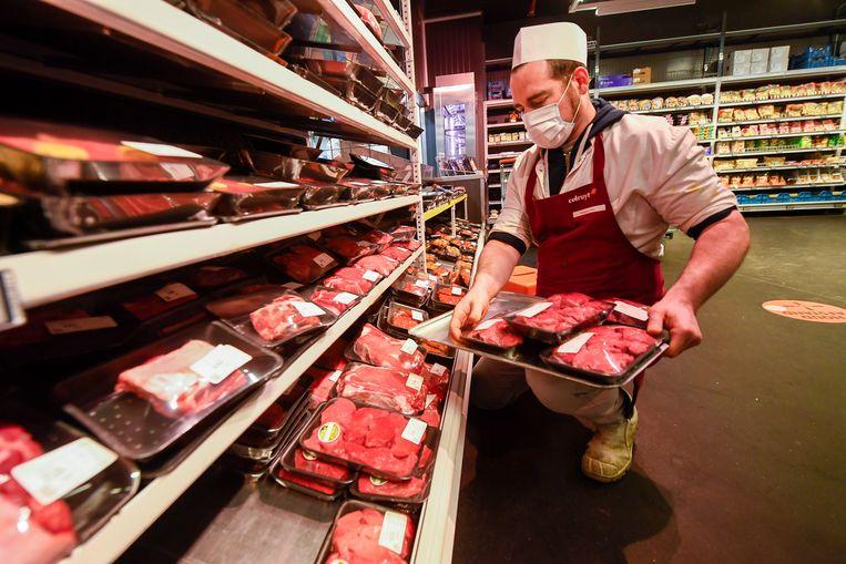Een medewerker van Colruyt vult de vleestoog aan. De warenhuisketen zegt dat virusdeeltjes in hun koelruimtes verwijderd worden door het vocht in de lucht te laten bevriezen.  Beeld Photo News