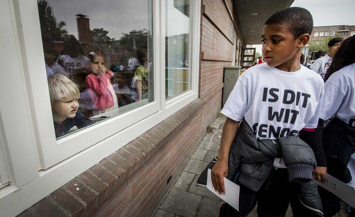 """Leerlingen van een Amsterdamse basisschool in witte t-shirts met de tekst: ,,Is dit wit genoeg voor u?"""", gingen recent langs de deuren om meer witte kinderen voor de school te werven"""