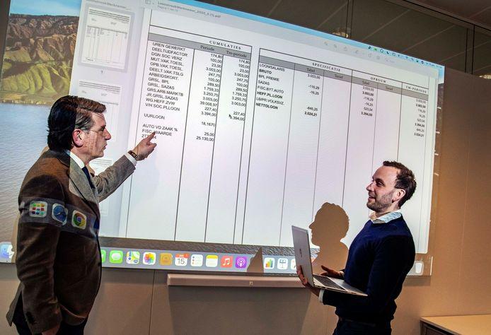 Directeur Arnold Barendrecht (l) en consultant Igor Timmermans bespreken een uitvergrote salarisstrook.