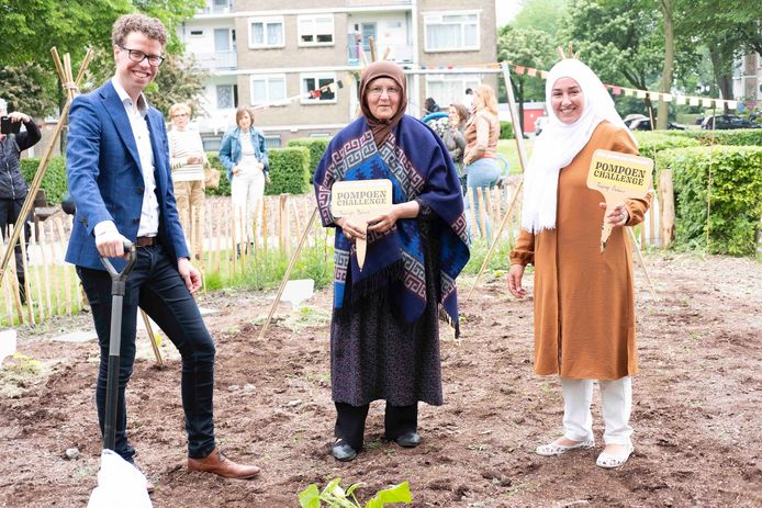Martijn Balster plant reuzenpompoen met deelnemers.