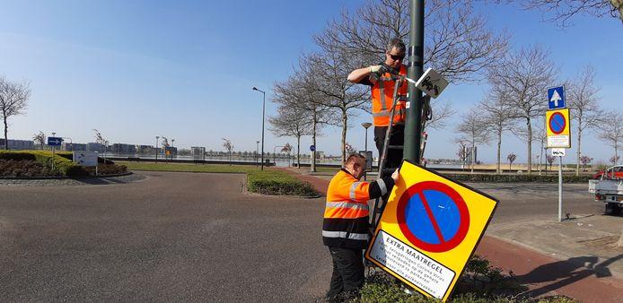 Medewerkers van het team Verkeer van de gemeente Bergen op Zoom hangen de parkeerverbodsborden nu aan lantaarnpalen