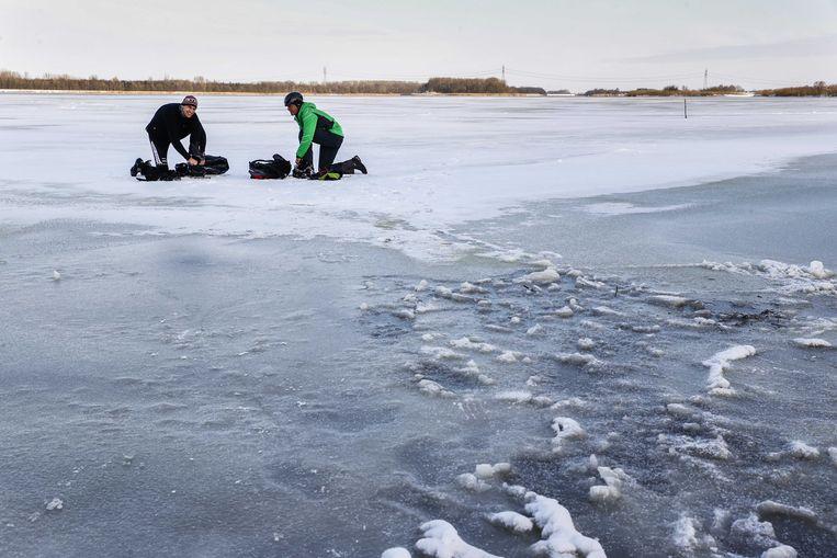 De eerste toerrijders binden de schaatsen onder op het Veluwemeer.  Beeld ANP