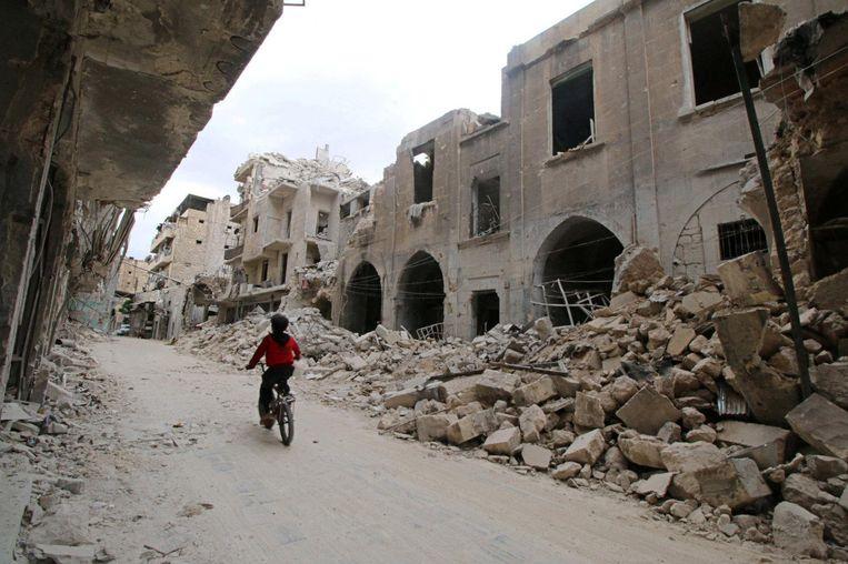 Een jongen rijdt door de verwoeste straten van de oude binnenstad van Aleppo.