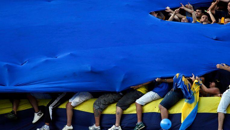 Supporters van Boca Juniors verstoppen zich onder een grote vlag.
