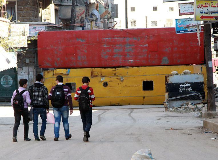 Scholieren lopen richting een muur van opgestapelde bussen in de Bustan al-Qasr buurt in Aleppo. Beeld getty