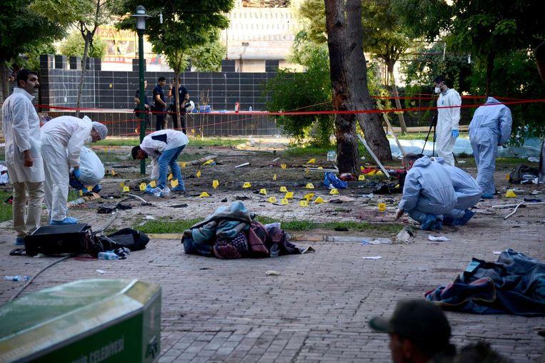 Forensische experts onderzoeken de tuin van het culturele centrum in Suruç, waar de aanslag plaatsvond. Beeld AFP