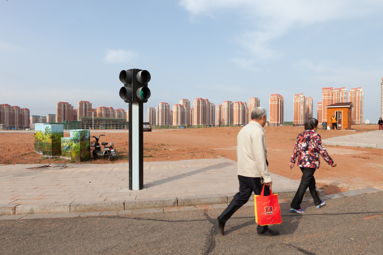 Passanten in Ordos passeren een nieuwe lege woonwijk.