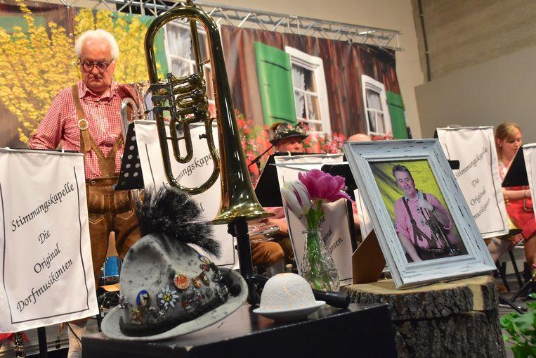 Centraal vooraan op het podium stond een foto van de overleden stichter/bezieler Marc Debruyne, met zijn typische Alpenhoed en een instrument.