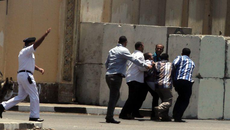 Mannen helpen een gewonde bij het paleis in Caïro. Beeld epa