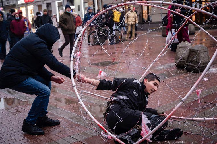Een politieman in burger arresteert activist Pavel Krysevich tijdens protesten zaterdag in Moskou.  Beeld AP