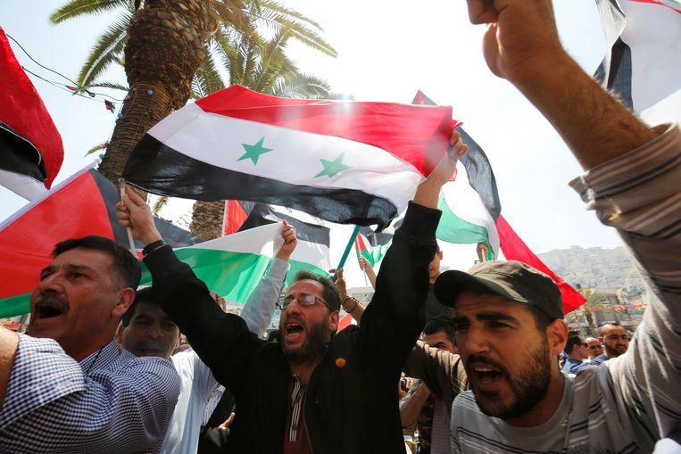 Demonstranten staan op hun vrije zaterdagochtend te dansen voor Assad. Beeld Reuters