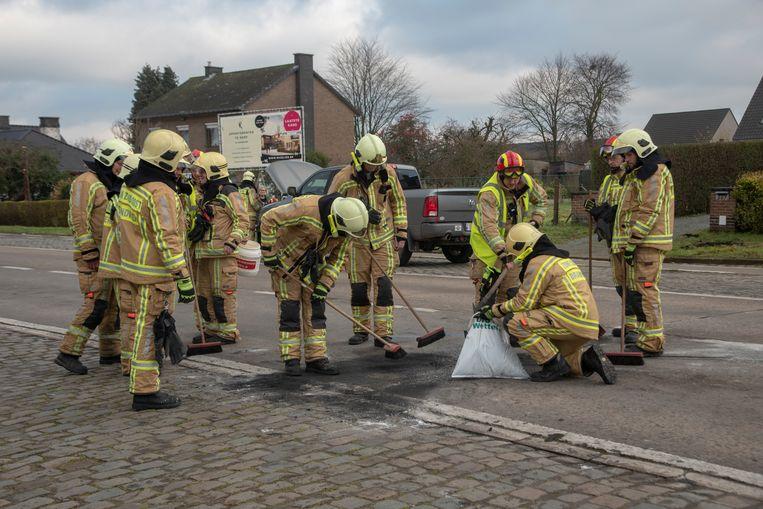 De brandweer ruimt de rijbaan op.