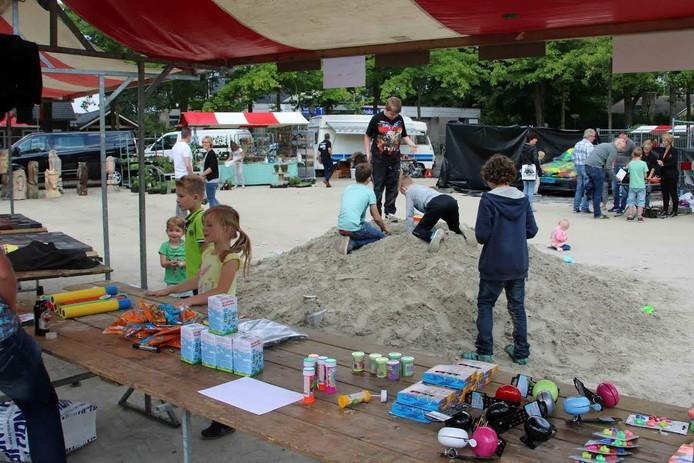 De jeugd speelt in het zand voor een spullenkraam