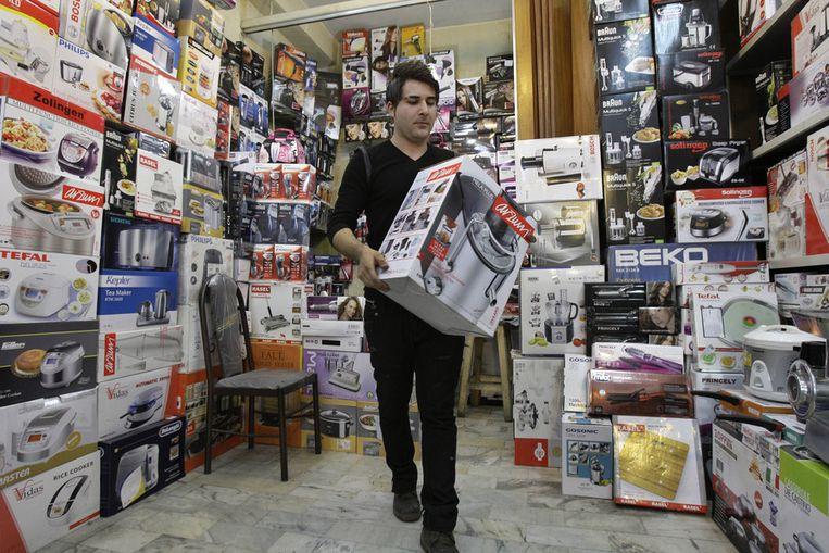 Een winkelier in Teheran. Winkels hebben het steeds moeilijker om de voorraad op peil te houden als gevolg van de Westerse sancties tegen Iran. Beeld ap