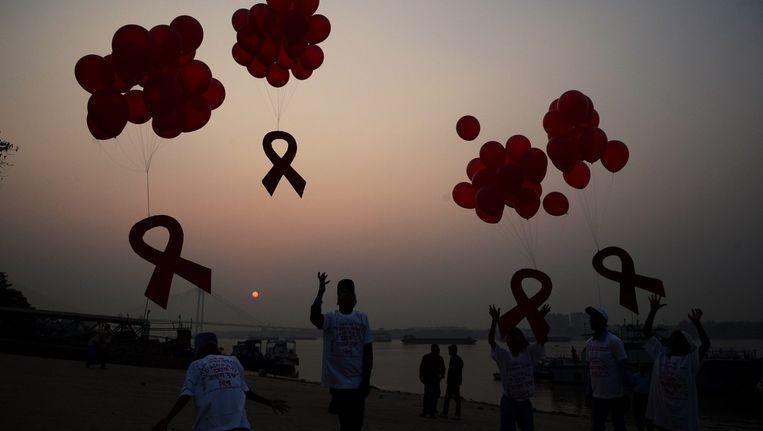 Ballonnen met het rode lintje, symbool voor solidariteit met mensen met hiv, worden opgelaten voor Wereldaidsdag in India. Beeld null
