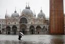 Een man maakt een foto van het overstroomde San Marco-plein.
