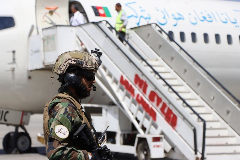 Een Talibanstrijder zondag bij een vliegtuig op Hamid Karzai International Airport. Zaterdag werd het vliegverkeer deels hervat. Beeld EPA
