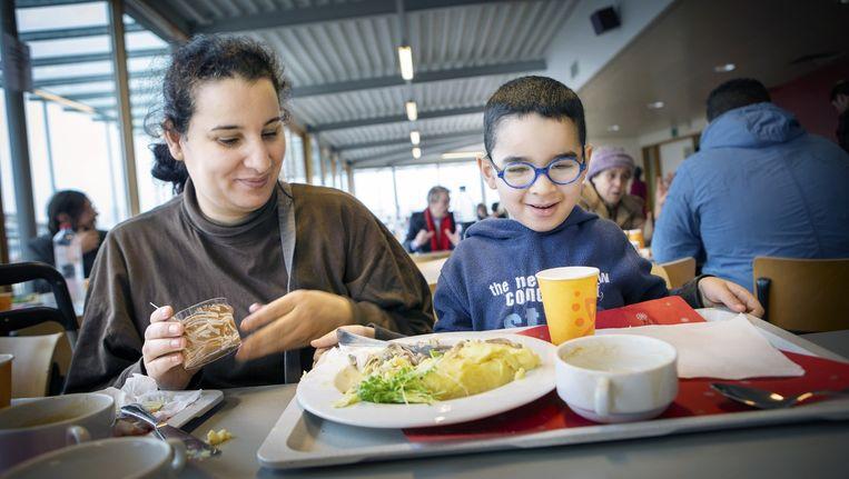 Een kansarm gezin geniet van een maaltijd voorzien door voedselbedelingsproject innocenti in Brussel. Beeld Yann Bertrand