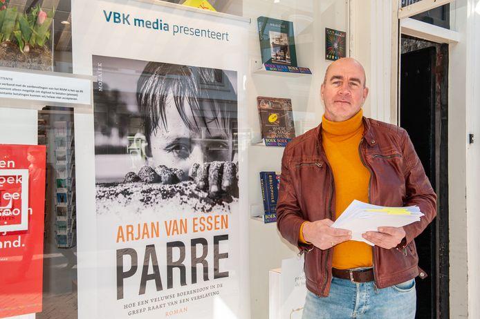 Arjan van Essen met de drukproef van zijn boek in handen.