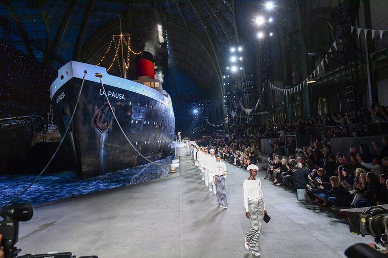 De cruiseshow in het Grand Palais. Links een kolossaal cruiseschip, rechts de modellen in scheepvaart-geïnspireerde outfits.  Beeld Getty Images