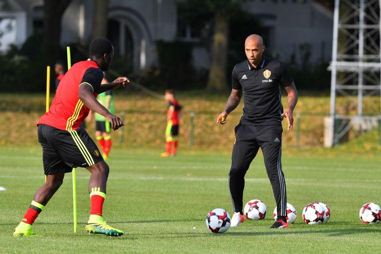 Thierry Henry (rechts) en Romelu Lukaku tijdens een trainingssessie van de Rode Duivels in augustus. Beeld BELGA