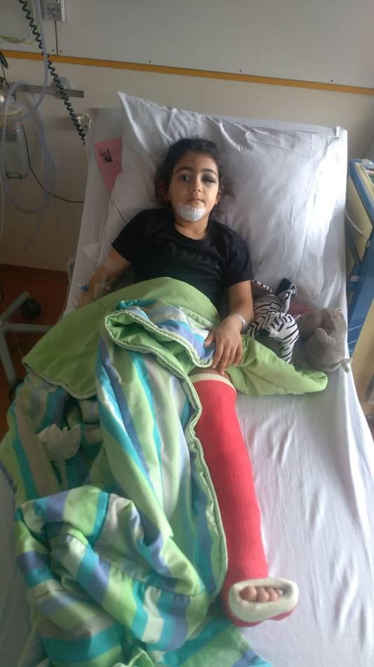 Basma (7) uit Doetinchem met gebroken been en verwondingen aan haar gezicht in het ziekenhuisbed.