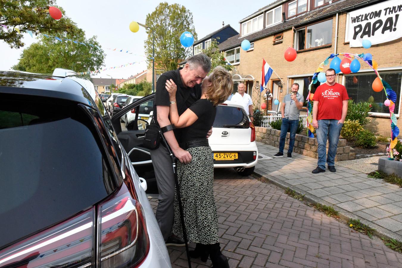 De van corona genezen Ron van Stein wordt bij thuiskomst omhelsd door zijn vriendin Ans Roest.