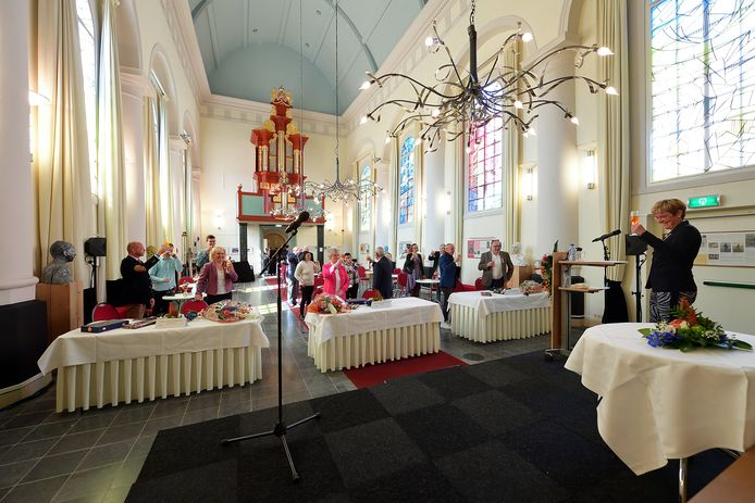 Burgemeester Miranda de Vries heft in de Van Goghkerk het glas met de zes Etten-Leurenaren die maandag een lintje ontvingen.