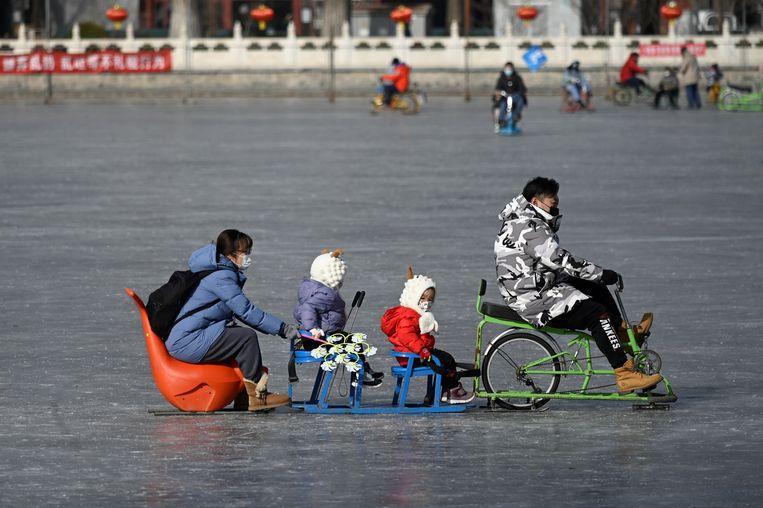 In Peking ligt wél al ijs. Het hele gezin kan op de slee achter deze inventieve fietslocomotief.   Beeld AFP