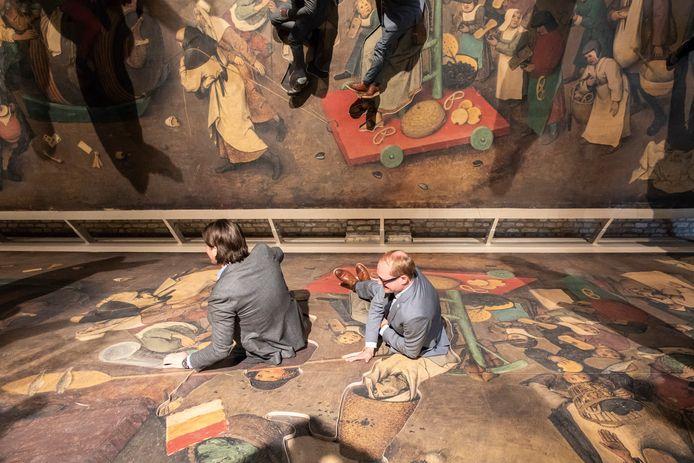 """Minister Weyts en gedeputeerde Philtjens gingen letterlijk liggen in één van de puzzelstukken die uit het schilderij waren gesneden. Bezoekers kunnen met een game zoeken naar voorwerpen die verdwenen zijn uit het doek """"De strijd tussen carnaval en de vasten""""."""