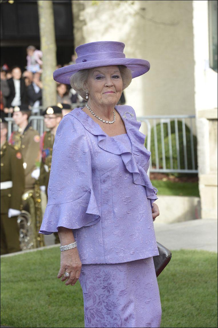 Koning Beatrix met opvallende hoed en losvallende outfit in een fel kleurtje. Beeld Photo News
