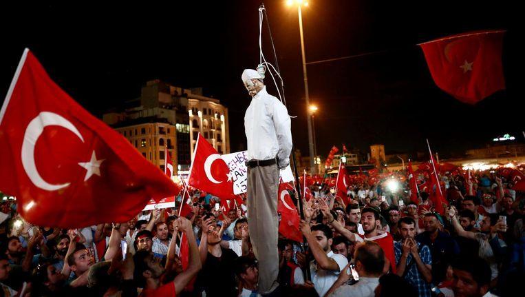 Pro-Erdogan demonstranten dragen een pop van de islamitische prediker Gülen met zich mee tijdens een demonstratie op het Taksim plein in Istanbul op 18 juli. Beeld epa