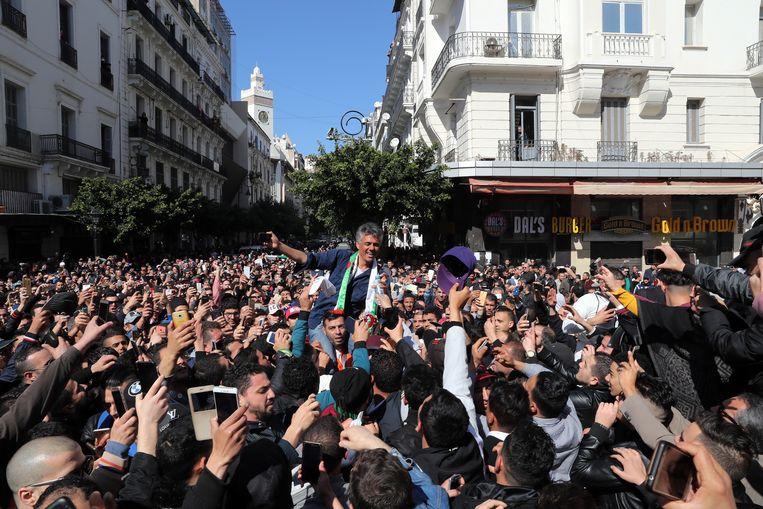 Demonstranten zaterdag in Algiers. Op de schouders Rachid Nekkaz, zakenman en een van de tegenkandidaten van president Abdelaziz Bouteflika bij de verkiezingen van 18 april. Beeld EPA