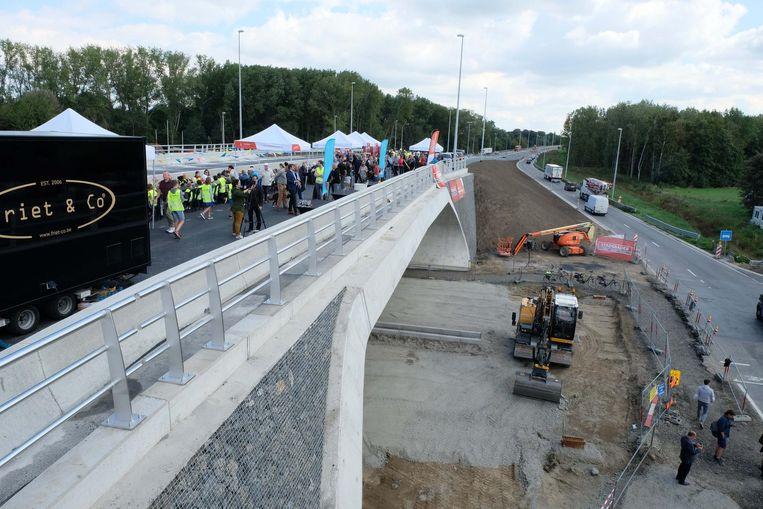 Op de nieuwe brug wordt er gefeest, eronder zijn de werken nog niet klaar.