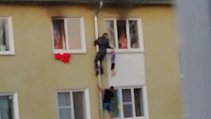 Buurtbewoners klimmen via de regenpijp naar boven om de kinderen uit de brand te redden.