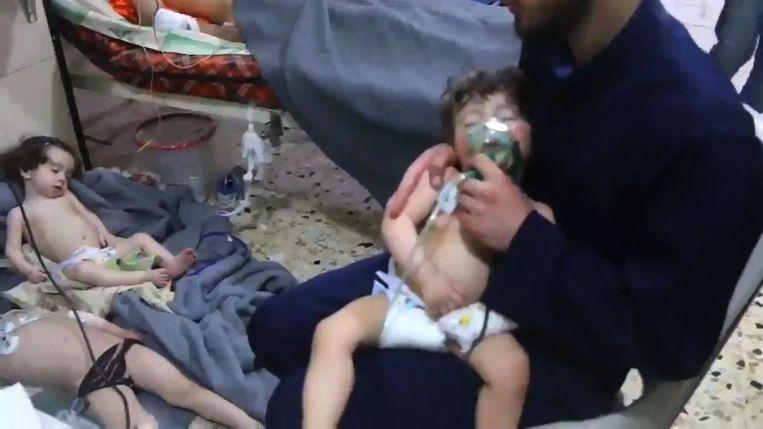 Kinderen krijgen medische hulp na een gifaanval in de buurt van Douma in april. Beeld AFP
