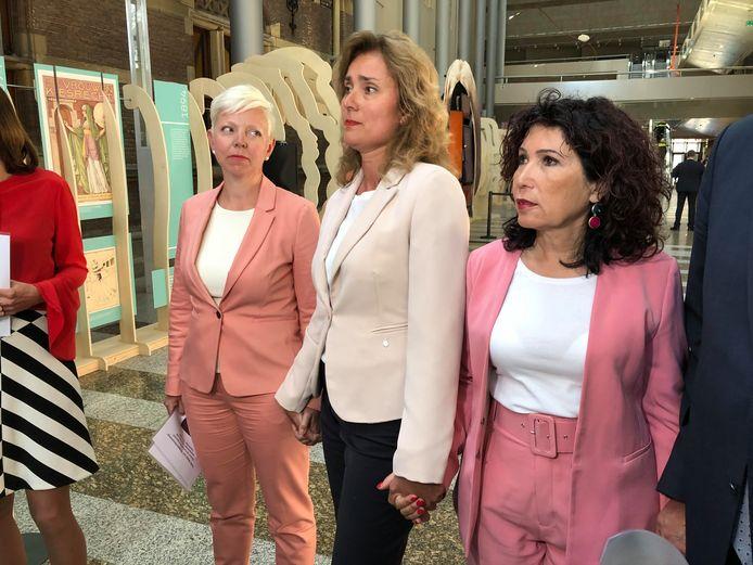 Kamerleden Kirsten van den Hul (PvdA), Vera Bergkamp (D66) en Nevin Özütok (GroenLinks) staan uit protest hand in hand bij de aanbieding van een anti-homopetitie