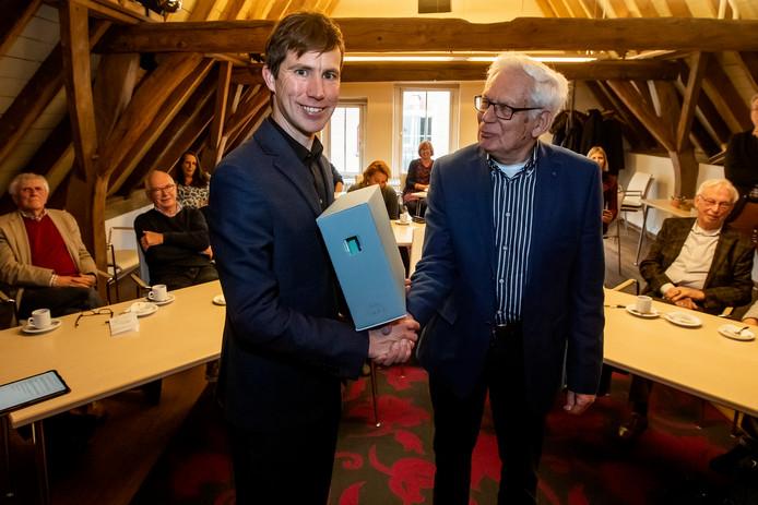 Jan de Vries overhandigt een archiefdoos aan directeur HCO Vincent Robijn. Het archief van Thomassen en Drijver is van 200 meter naar 50 meter teruggebracht en wordt overhandigd aan de Athenaeumbibliotheek.