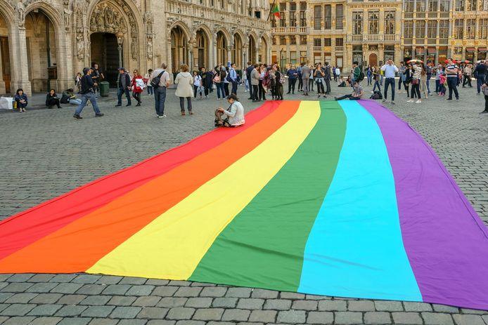 Grote regenboogvlag op de Grote Markt kondigt het festival aan.