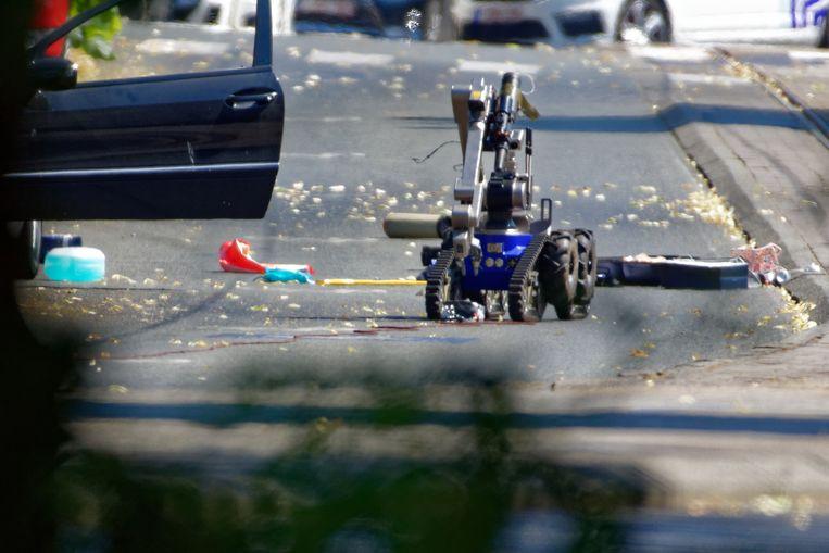 Speciale eenheden rijden de wagen met de bom klem in Sint-Pieters-Woluwe. DOVO probeert met een robot het springtuig onschadelijk te maken.    Beeld BELGAIMAGE