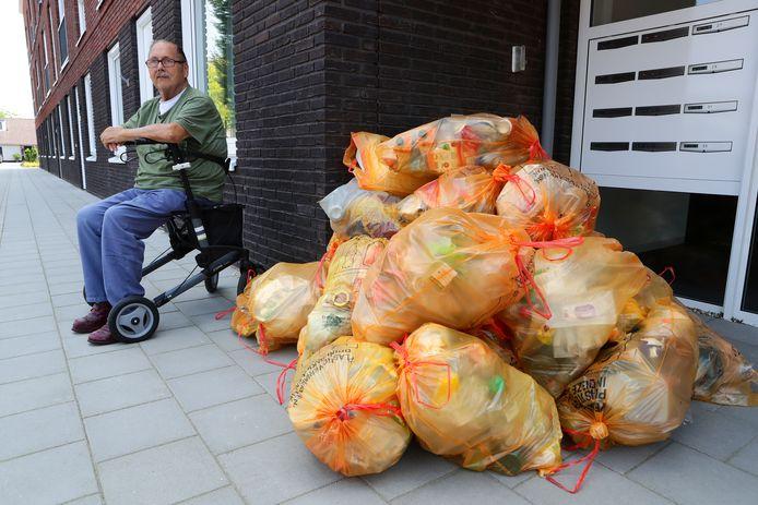 Rien van Ooijen voor de deur van zijn complex. Samen met een berg keurig gescheiden plastic afval.