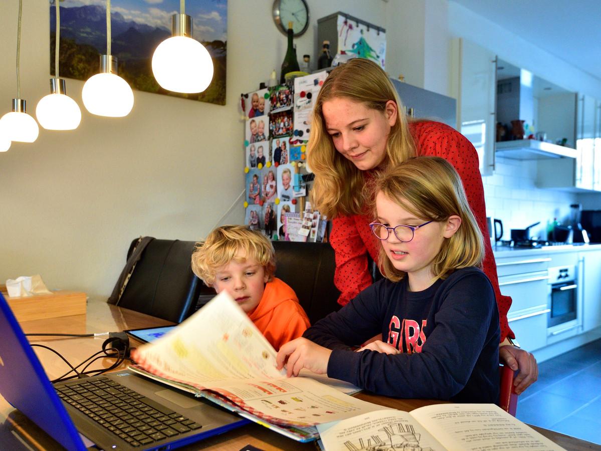 Elisa helpt haar neefje Bram en nichtje  Merel met hun schoolwerk.