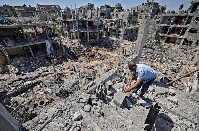 Een Palestijnse man doorzoekt het puin in Beit Hanun, een plaats in het noorden van de Gazastrook. Heel wat gebouwen werden er vernield door een Israëlische luchtaanval.
