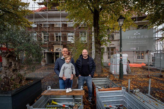 René Vermeulen (R) en Piet Jansen (L) met kleinzoon Augusta voor het Spuihuis dat de komende maanden volledig achter de steigerpijpen verdwijnt.