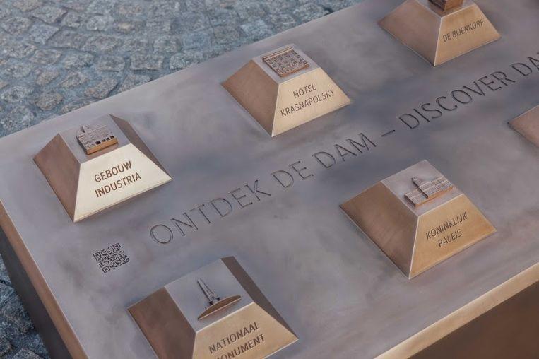 Het bronzen kunstwerk heeft bovenop ieder 'plateautje' een gebouw van de Dam in 3D, met tekst en braille. Beeld Jurre Rompa
