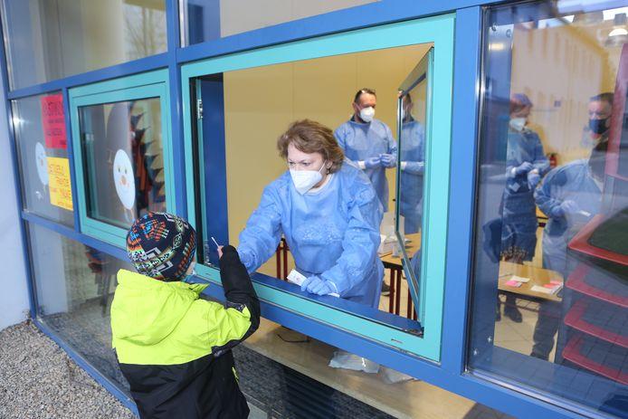 Een scholier geeft zijn neusstaal af aan een medewerker in een testcentrum in een basisschool in Sachsen-Anhalt. Vanaf vandaag worden er in alle scholen in die deelstaat sneltesten uitgevoerd.
