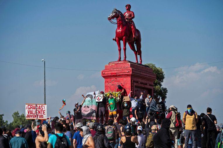 Betogers verzamelen zich rond het beeld van Manuel Baquedano. Beeld AFP